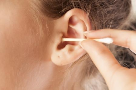 девушка чистит уши палочкой